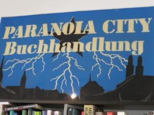 Paranoia City Buchhandlung: ein altes Firmenschild mit schwarzem Fünfzackstern, daraus hervorschiessenden Blitzen über den Altstadtdächern von Zürich