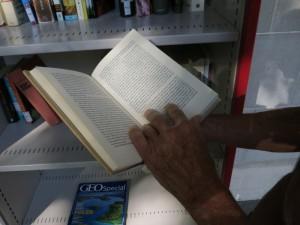 Buecherschrank der Pestalozzibibliothek Zürich: ein eifriger Leser blaettert in einem Buch