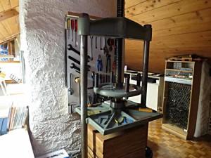 Werkzeuge für den Buchbinder: eine Schlagpresse, ein Kasten mit Stempeln fürs Vergolden