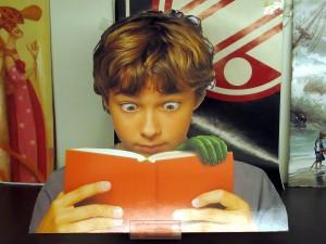 Der kleine Junge mit dem Buch, aus dem eine grüne Hand waechst