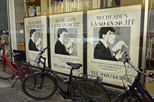 Logo der Buchhandlung als Plakat, Velos vor den Schaufenstern