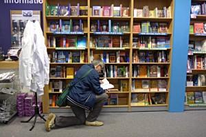 Mann kniet vor Büchergestell und blättert in einem Buch