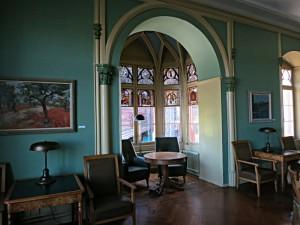Grüner LesesaalIm grünen Lesesaal: runde und eckige Tische, Fauteuils und Stühle, Leselampen
