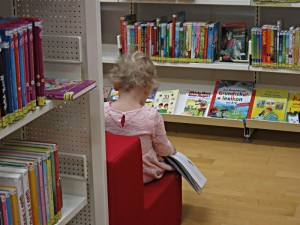 Jüngste Leserin mit Buch auf den Knien