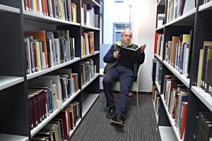Lesender im Fauteuil zwischen den Gestellen