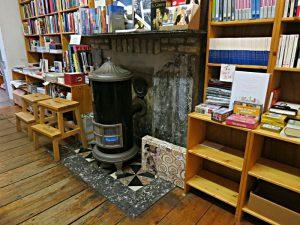 Metallofen mit Gasheizung, Treppchen zum Erreichen der oberen Tablare, Bücher soweit das Auge reicht