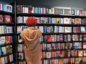 """LaFeltrinelli Buchhandlung, Leserin vor den Büchergestellen """"Narrativa"""""""
