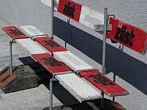 Eine einfache Sitzbank aus Bauabsperrbrettern mit dem Namen Züst darauf
