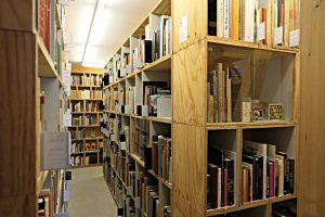Schmale Gänge zwischen den Bibliotheksgestellen aus Holzkisten