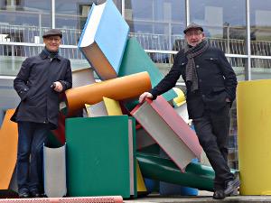 Die zwei Buchortisten in Brig vor Bücherskulptur