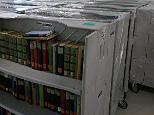 Rollwagen mit Büchern, eingehüllt in Plastikfolie
