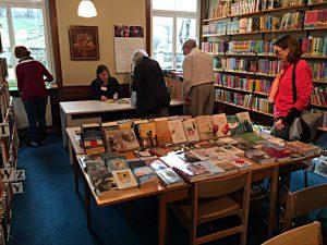 Tische mit neuen Büchern, Besucherinnen und Besucher