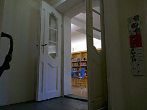 Blick vom Treppenhaus in einen Bibliotheksraum