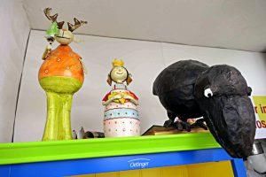 Lustige Wesen schauen von den Gestellen: ein Rabe, ein Elch mit goldenem Geweih und ein Prinzessin mit drei goldenen Herzen