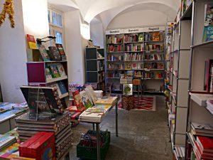 Teil des ehemaligen Klosters: weisse Decke, Steinboden, viel Platz für Kinderbücher