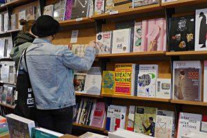 Kundinnen vor dem Gestell mit Büchern zu Design