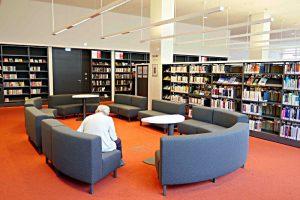 zahlreiche Sitzgelegenheiten, dunkle Büchergestelle, starkes Leselicht