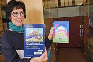 Ines Thoermer zeigt Bücher, die in Zusammenarbeit mit Schulklassen entstanden sind