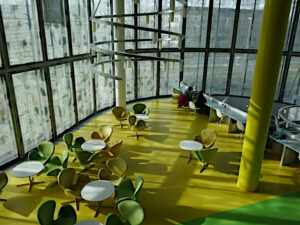 Ruhezone: grüne Sessel, gelber Boden, Arbeitsplätze